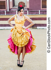 Woman, model of fashion, wearing a dress in a bullring -...
