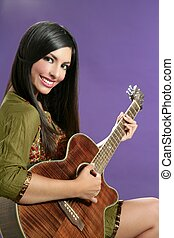 Beautiful brunette playing acoustic guitar over purple...