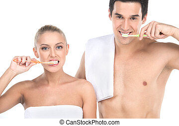 Close up of sexy fit man and woman brushing teeth with toothbrushes. Standing couple isolated over white background looking into camera