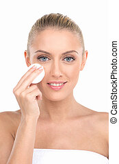 Portrait of beautiful young girl applying on face cosmetic...