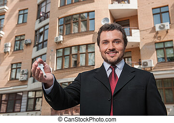adult man holding key to dream house isolated on building...