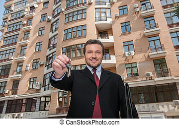 adult man holding key to dream house with building on...