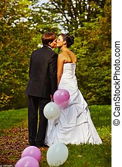 Wedding day - young couple is walking in park