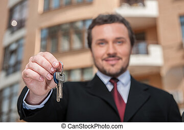 closeup on adult man holding key to dream house with...