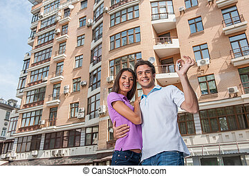 Couple in front of new home holding door keys. man hugging...