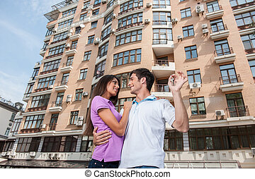 Couple in front of new home holding door keys and looking at...