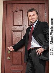 realtor opening wooden door and smiling. brown wooden door...