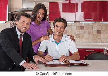 Couple of happy buyers signing agreement on new house young...