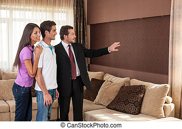 man real estate agent showing couple new house. male agent...