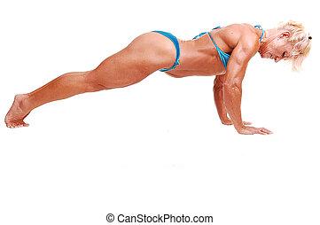 Woman doing pushups - A blond muscular woman doing pushups...