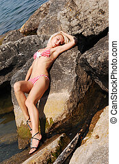 Bikini girl on the rocks - A blond young woman in an red and...