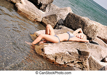 Bikini girl on the rocks.
