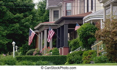 Small town America - LS across four front yards of victorian...