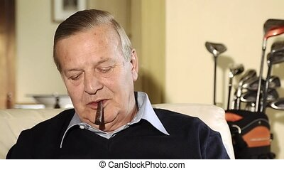 senior man smoking cigar - Senior man relaxing at home