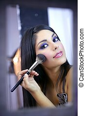 Indian fashion model makeup with brush on the mirror