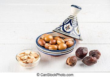 Argan fruit in a moroccan tajin - Argan Fruit on a wooden...