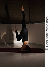 Head stand in dark gym - Redhead woman exercising head stand...