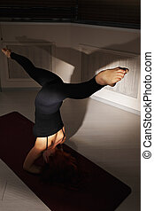 Head stand with split in dark gym - Redhead woman exercising...