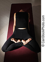 Woman legs crossed exercising yoga above view