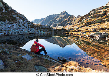 Male hiker takes a rest sitting next a mountain lake. Autumn...