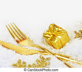 Christmas golden cutlery and ornaments on snow