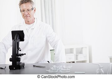 scientific researcher with microscope - portrait of male...