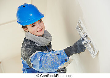 Plasterer at indoor wall work - female plasterer painter at...
