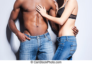 True sensuality. Close-up of beautiful young couple in jeans...