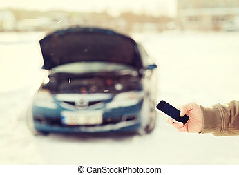 closeup of man with broken car and smartphone -...