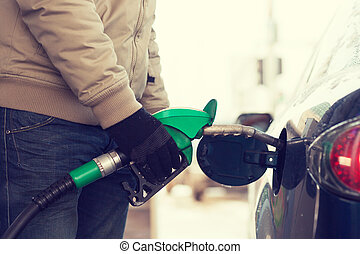 close up of male refilling car fuel tank - vehicle and fuel...