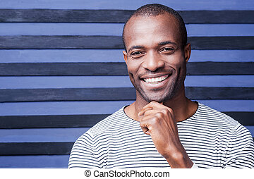 I think I like you. Happy young African man holding hand on chin and smiling while standing against striped background