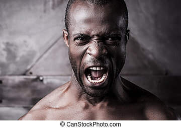 Furious and aggressive. Portrait of furious young shirtless...