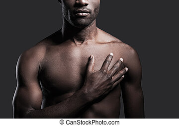 It is in my heart. Cropped image of young shirtless African...