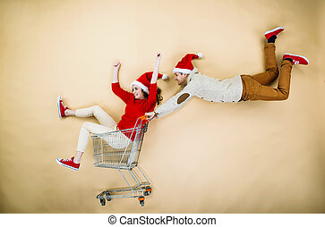 Christmas couple with trolley on beige background - Young...