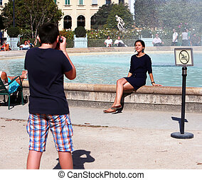 Teenage boy photographing girl, that sitting on the fountain