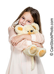 Girl hugging a toy bear - Little girl in a beige dress with...