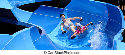 Mother and child having fun in water park - Young mother and...