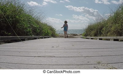 Little Girl runs down path to beach
