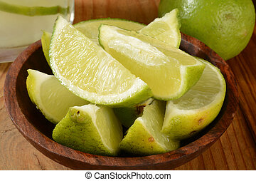 Bar fruit - Fresh lime wedges in a wooden bowl with a gimlet...