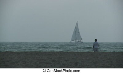 Man on Beach Watches Sailboat - A man watches a boat sail by...