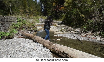 Brave girl crossing a river in a forest