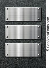 three stainless steel metal plates on black background -...