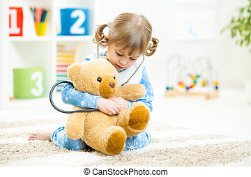 Cute little girl playing doctor with plush toy at home -...