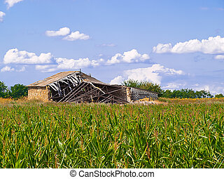 Old barn in the middle of a green field against clouds