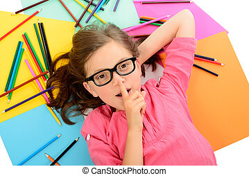 young schoolgirl with glasses lying on the floor amid of colored