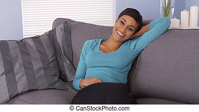 Pretty African woman relaxing on couch