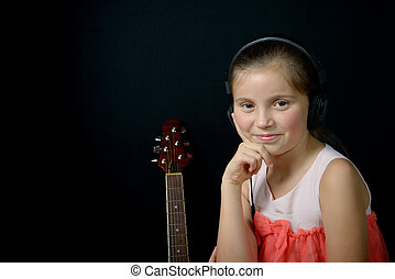a little girl listening to music with headphones and smile