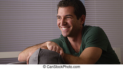 Cheerful guy sitting on couch