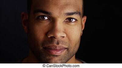 Headshot of black man looking at camera