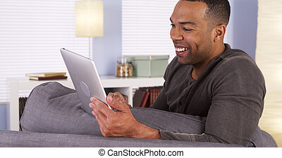 Black man video chatting on tablet